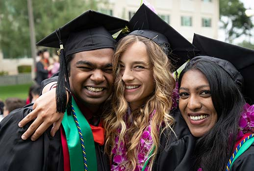 A man and two women students dressed in cap and gown celebrate graduation at Santa Clara University