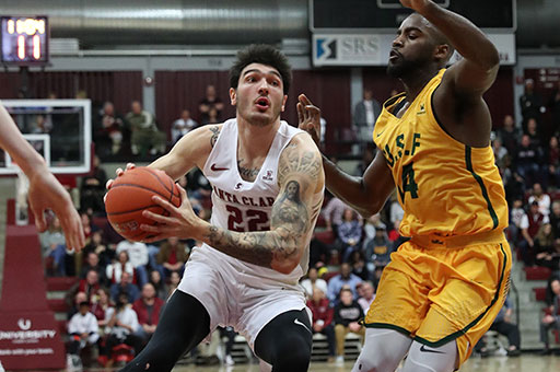 A Santa Clara basketball player drives past a University of San Francisco defender toward the basket