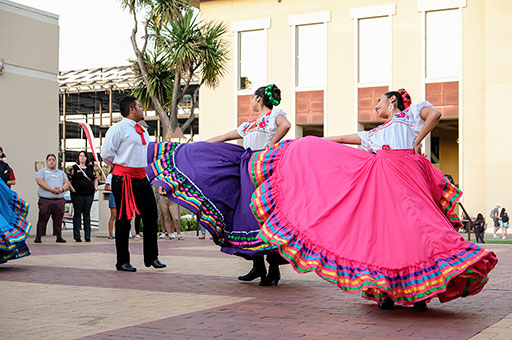 Members of the Mexican folk dancing club on campus perform outside of the library during a campus celebration