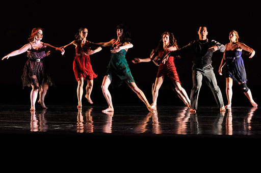 Silhouettes of student dancers on stage during a rehearsal for a Santa Clara University performance