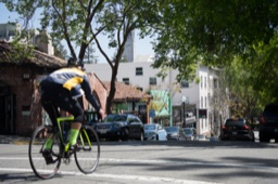 a bicyclist rides down the street in front of shops in Berkeley